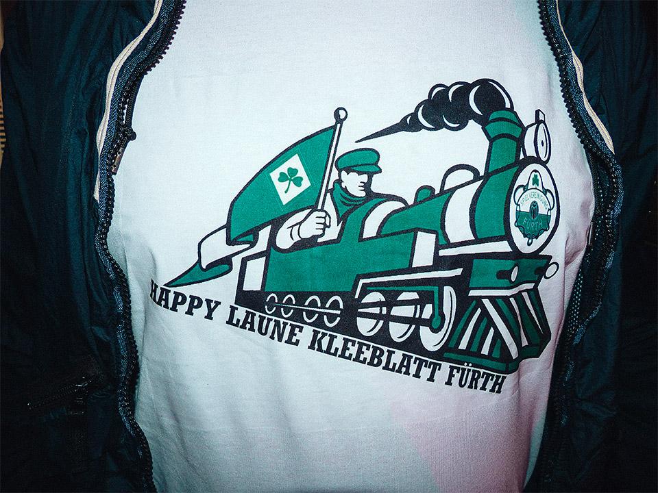 """T-Shirt mit dem Aufdruck """"Happy Laune Kleeblatt Fürth"""" unter dem Bild einer weiß-grünen Dampflokomotive."""